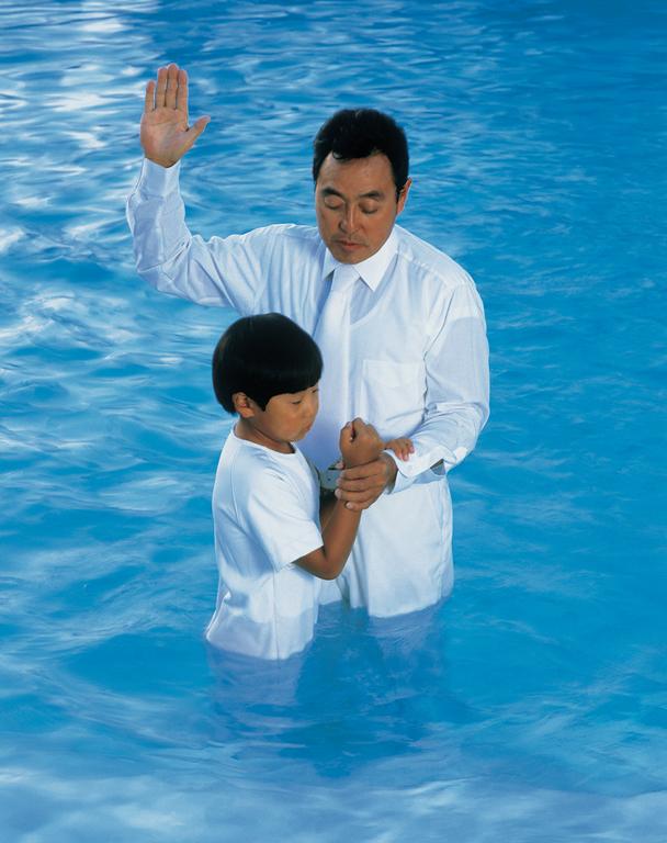 バプテスマを受ける男の子と施す父親