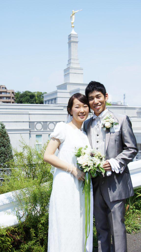 福岡神殿の前に立つ結婚したての夫婦