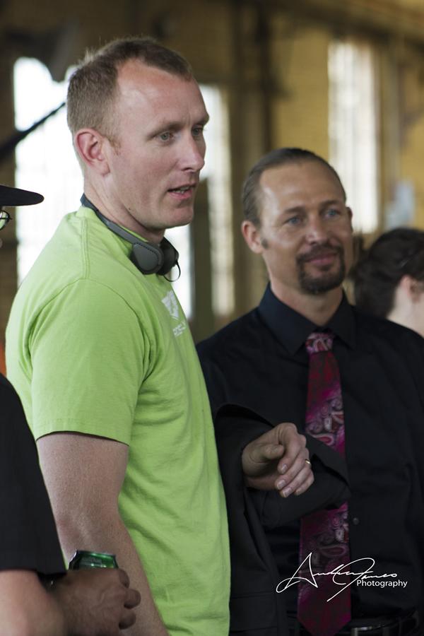 脚本家であり監督のアダム・ホワイトが「閃いた銃」の撮影所で プロの殺し屋役のトム・ポーストと