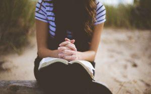 膝のうえに置かれた聖典の上で手を組む女性