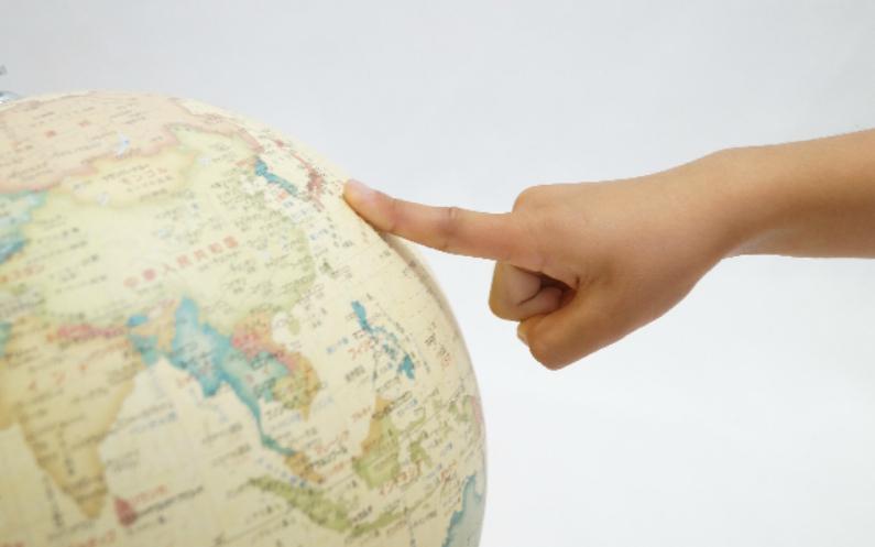 地球儀を指差す手