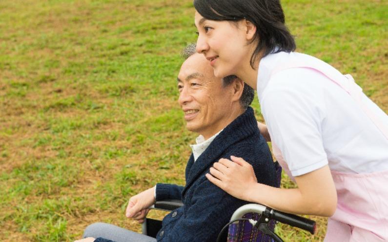 車椅子の男性を助ける女性