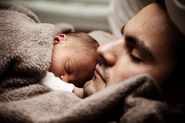 父親が生まれたばかりの赤ちゃんと毛布をかけで休む様子