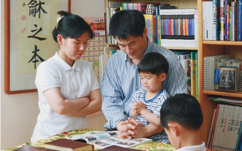 家庭で祈るモルモン教の家族