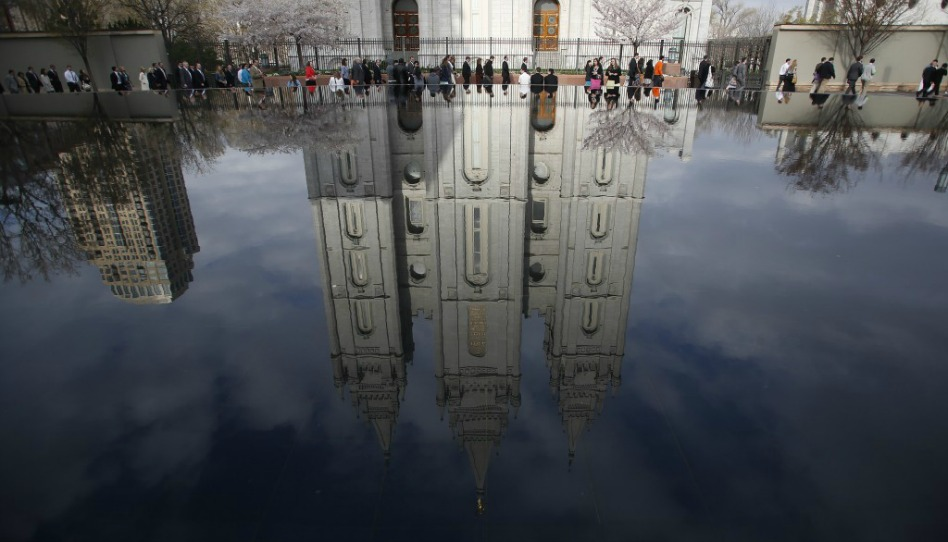 カンファレンスセンターに向けてソルトレーク神殿の前を歩く人々が水面に反射した様子
