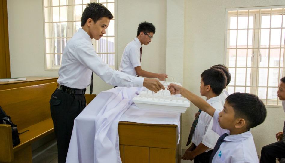 モルモン教会で聖餐をパスする神権者の青少年
