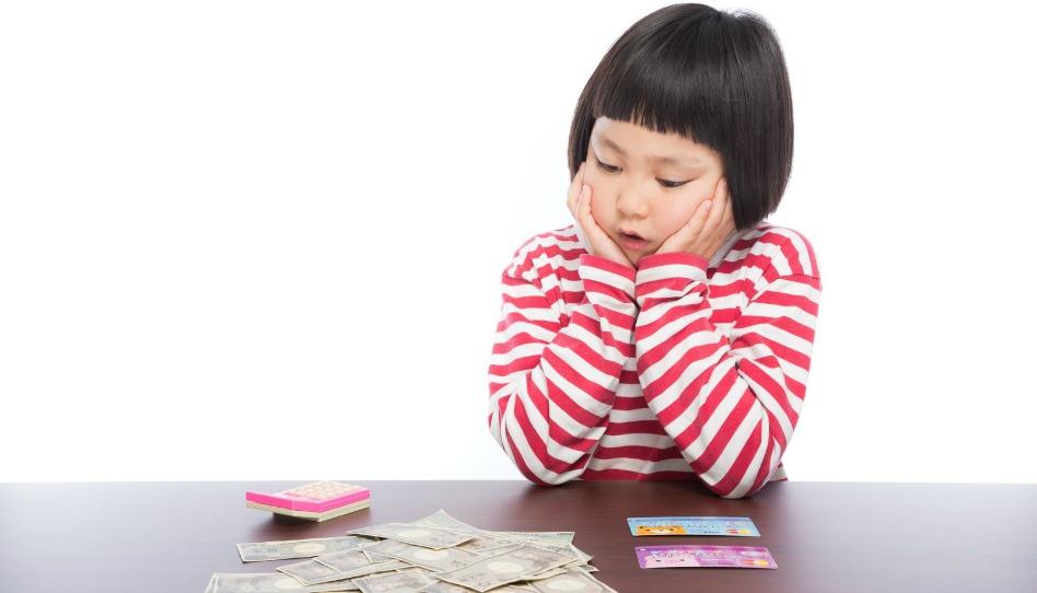 金銭教育を受けてお金を眺める6歳の子供