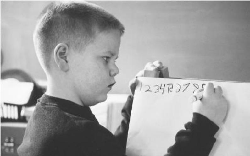数字を画用紙に書く12歳のジェレミー