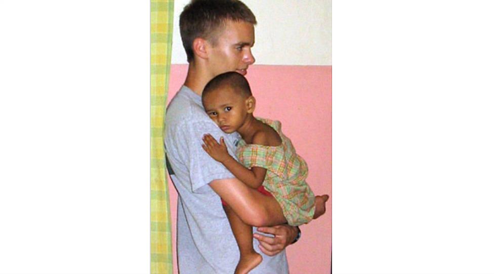 少年の腕の中でリラックスした様子の女の子の赤ちゃん