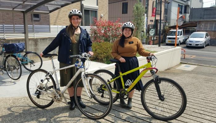 姉妹宣教師が自転車をそれぞれ持って並んで立っている様子