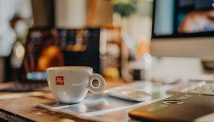 パソコンの前にあるカップ