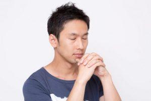 手を組んで静かに目をつむり祈る男性