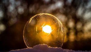 雪の上で傾いた太陽の光を受け光る透明な玉