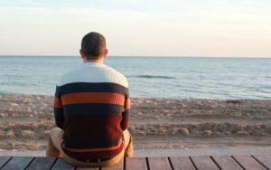 砂まで座っている後ろ姿の男性