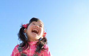 透き通る青い空をバックに満面の笑顔の女の子