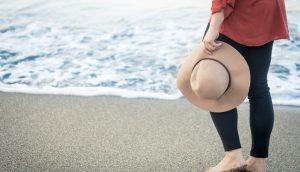 砂浜の波打ち際を裸足で歩く女性