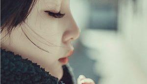 目を閉じて手を組んで祈っている横顔の女性