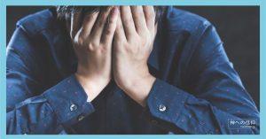 手で顔を覆い悩む男性